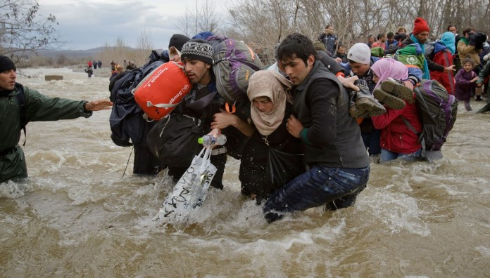 Migrants crossing river photo