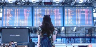 Woman at airport checking flights information board for delays