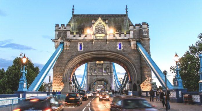 London car traffic crossing tower bridge at sunset