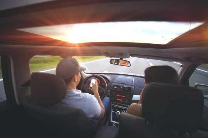 People using smartphone while driving car