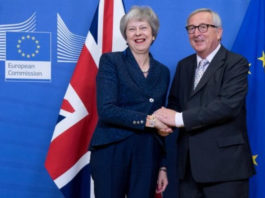 Theresa May shakes hands with EU chief Jean-Claude Juncker after agreeing the deal